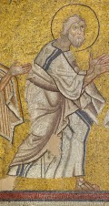 • This dynamic, striding figure is the sole survivor from a mosaic of the Communion of the Apostles in the apse of a church in northern Greece that burned in 1913. His beard and unkempt hair identify him as the apostle Andrew. Early photographs show that the full composition depicted two images of Christ behind the altar, distributing the bread and wine of the Eucharist to processions of apostles approaching from either side of the apse. The subject is the liturgical equivalent of the Last Supper. Mosaic of the apostle Andrew, late 11th–early 12th century, glass, gold, and stone tesserae, Archaeological Museum of Serres